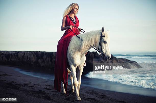 Woman rides along the beach on a horse