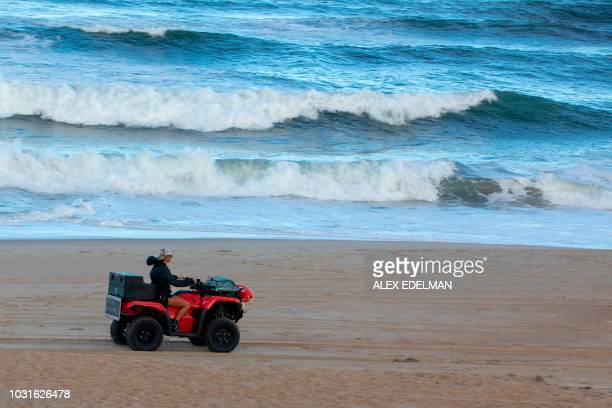 A woman rides an all terrain vehicle on the beach in Kill Devil Hills on the Outer Banks of North Carolina on September 11 as residents heed...