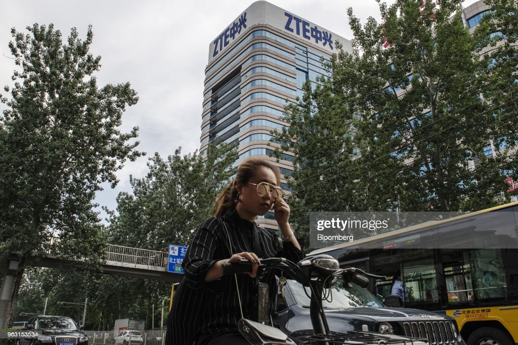 A woman rides an electric bicycle past a ZTE Corp. building in Beijing, China, on Thursday, May 24, 2018. PresidentDonald Trumpsaid the U.S. would allow Chinese telecommunications-equipment maker ZTE Corp. to remain in business after paying a $1.3 billion fine, changing its management and board and providing 'high-level security guarantees.' Photographer: Gilles Sabrie/Bloomberg via Getty Images