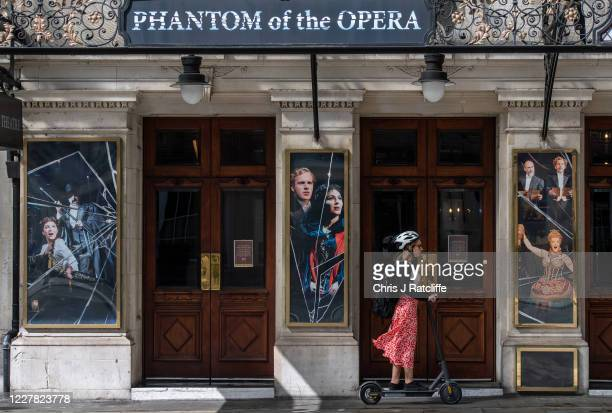 Woman rides an electric scooter past Her Majestys Theatre, home to Phantom of the Opera, on July 29, 2020 in London, England. Phantom of the Opera,...