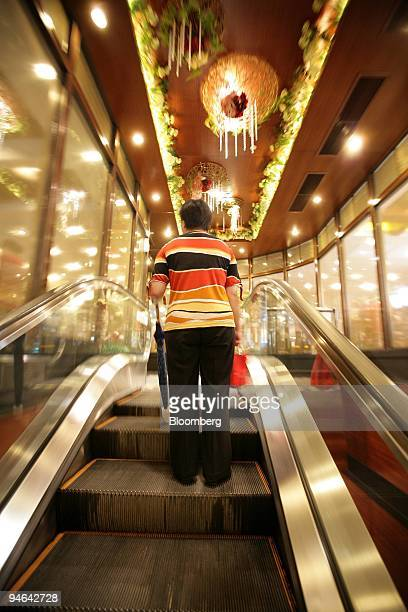 A woman rides an escalator leading to a Tao Heung restaurant in the Tseung Kwan O area of Hong Kong China on Tuesday June 5 2007 Tao Heung an...