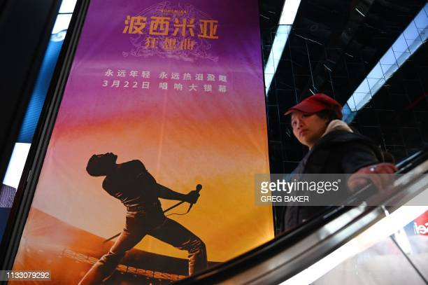 A woman rides an escalator past a poster for the film Bohemian Rhapsody at a movie theater in Beijing on March 27 2019 Scenes in the movie about rock...