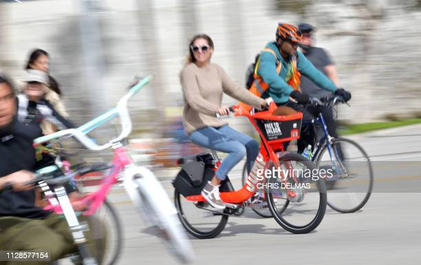 Woman rides an Uber JUMP e-bike in car-free streets during a CicLAvia event in Culver City on March 3, 2019. - CicLAvia is a non-profit organization...