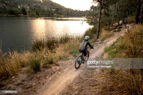 a woman rides away on a bike path by a lake at sunset - lakeshore stock pictures, royalty-free photos & images