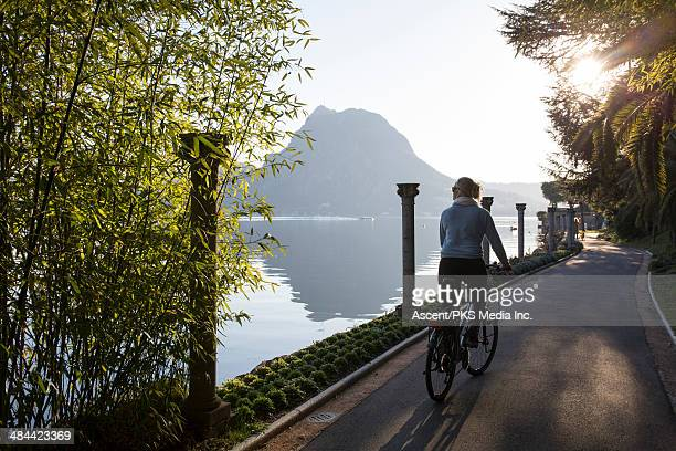 Woman rides bicycle along lake promenade