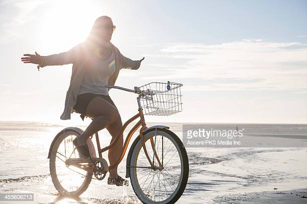 Woman rides bicycle on beach, without using hands