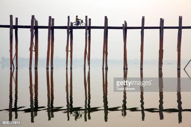 Woman rides bicycle on U Bein Bridge in Mandalay