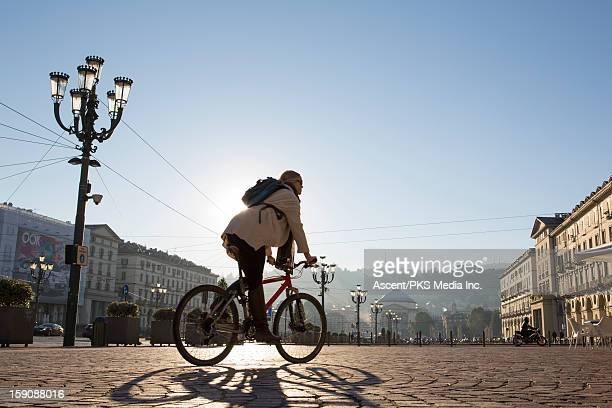 Woman rides bicycle through urban piazza, sunrise