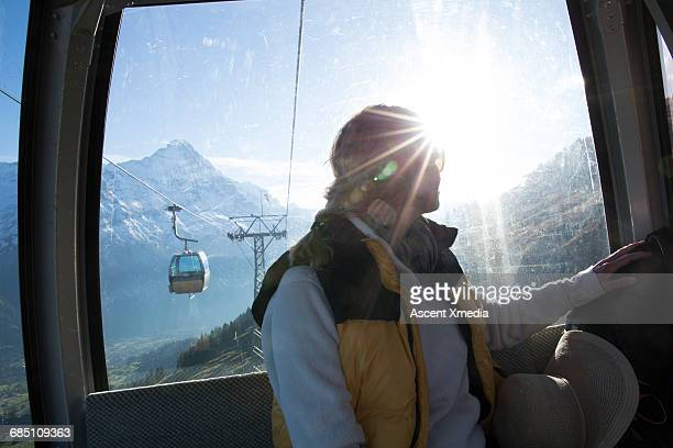 Woman rides cable car down mountain slop