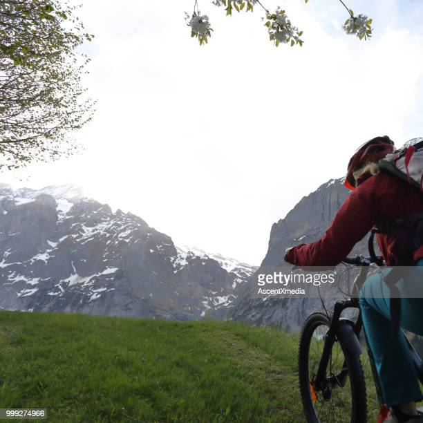 woman rides electric bike in the swiss alps - human powered vehicle stock photos and pictures