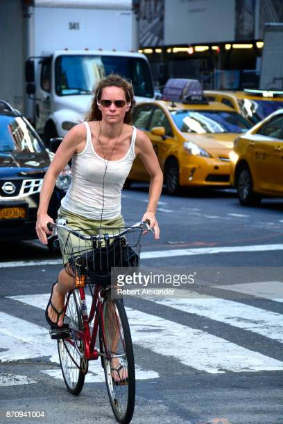 A woman rides her bicycle along Fifth Avenue in New York New York as she listens to her mobile device using a pair of headsets