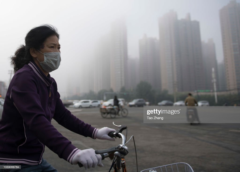 A woman rides her bicycle at the Changjiang street during dense fog enveloping Harbin on September 14, 2018 in Harbin, China. The meteorological department issued a yellow alert for dense fog