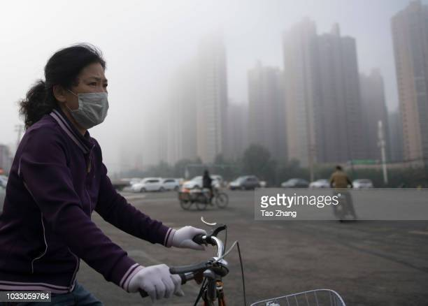 A woman rides her bicycle at the Changjiang street during dense fog enveloping Harbin on September 14 2018 in Harbin China The meteorological...
