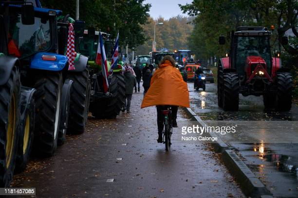 A woman rides her bicycle next to the tractors of the demonstration on October 16 2019 in The Hague Netherlands A demonstration has been called in...