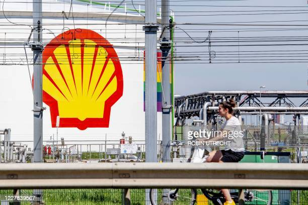 Woman rides her bicycle past the Shell Pernis site in Rotterdam on July 30, 2020. - Energy major Royal Dutch Shell posted on July 30, 2020 a colossal...