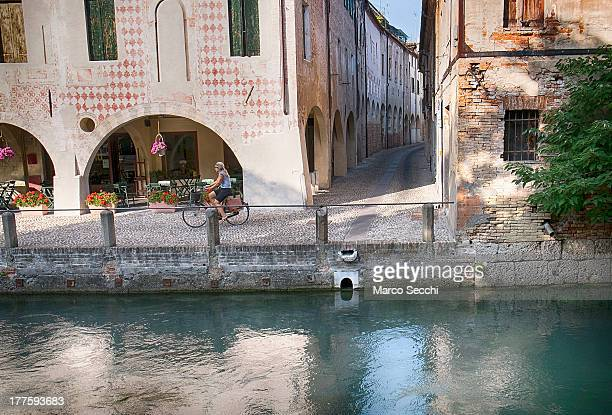 Woman rides her bike along a canal on a traditional part of Treviso on August 24, 2013 in Treviso, Italy. Treviso claims that Tiramisu was invented...