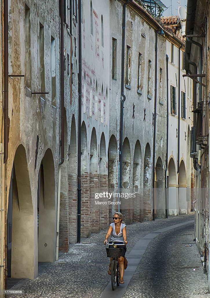 A woman rides her bike along a street on a traditional part of Treviso on August 24, 2013 in Treviso, Italy. Treviso claims that Tiramisu was invented in the 1960s by Alba Campeol, the owner of the restaurant called 'Alle Beccherie', who supposedly wanted to create a dessert that would give her an energy boost after the birth of her son.