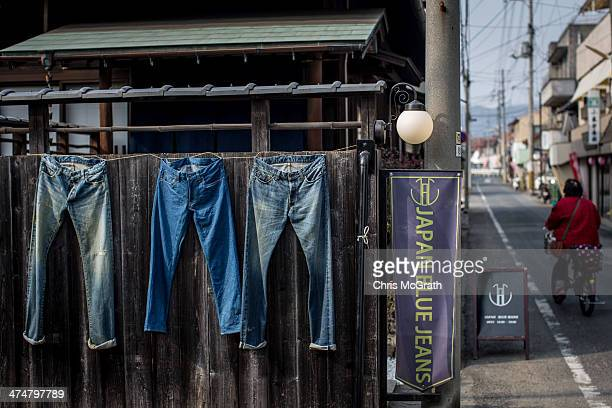 A woman rides her bike down Jeans Street in Kojima district on February 25 2014 in Kurashiki Japan Kojima is a small seaside district in the west of...