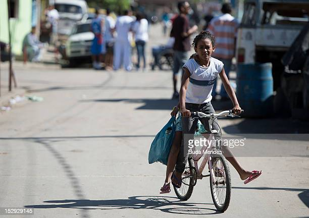A woman rides her bike during the official visit of David Cameron to Luta Pela Paz Project at Complexo da Mare on September 28 2012 in Rio De Janeiro...