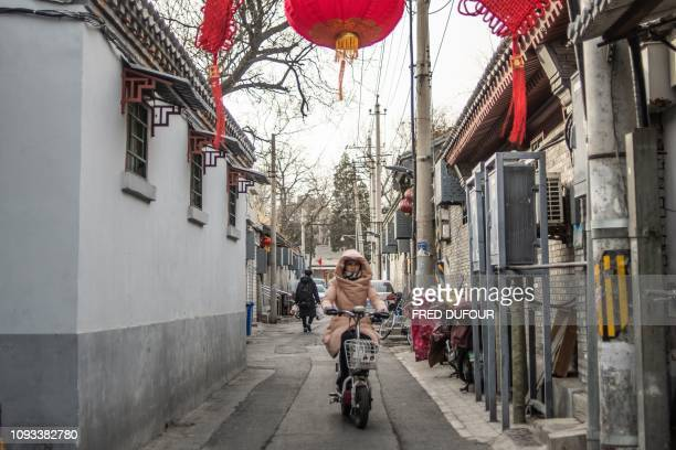 A woman rides her bike in a 'Hutong' traditional Beijing courtyards ahead of the upcoming Lunar New Year in Beijing on February 3 2019 Millions of...