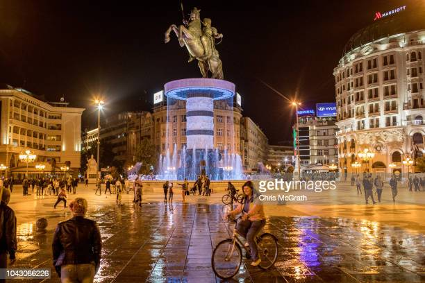 A woman rides her bike through a fountain in Macedonia Square on September 29 2018 in Skopje Macedonia Macedonians will go to the polls Sunday to...