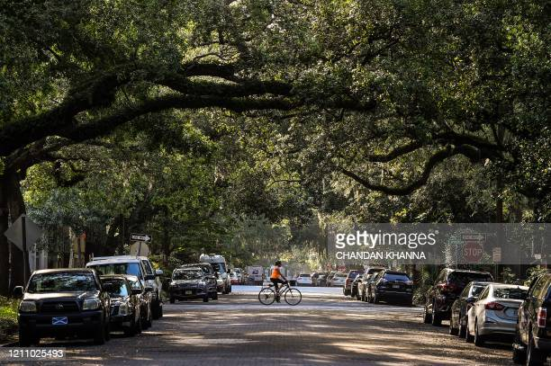 A woman rides her bike through the Historic District in Savannah Georgia amid the novel coronavirus pandemic on April 25 2020 After being locked down...