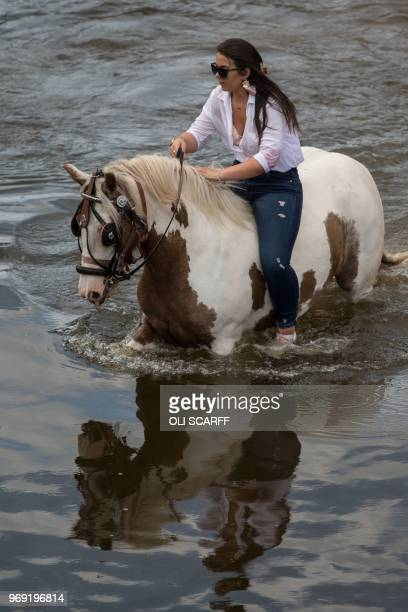 A woman rides her horse into the River Eden on the opening day of the annual Appleby Horse Fair in the town of ApplebyinWestmorland northwest England...