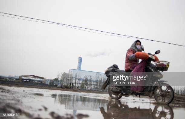 A woman rides her motorbike past a local incinerator in Gaojia in China's Shandong province on November 17 2015 AFP PHOTO / FRED DUFOUR / AFP / FRED...