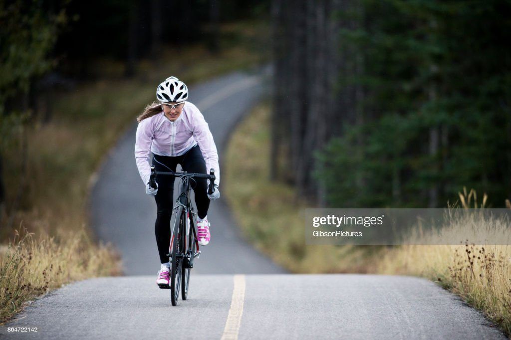 A woman rides her road bike along the Trans Canada Trail bikepath near Canmore, Alberta, Canada in the autumn. : Stock Photo