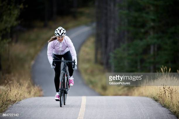 a woman rides her road bike along the trans canada trail bikepath near canmore, alberta, canada in the autumn. - cycling stock pictures, royalty-free photos & images