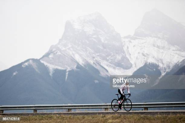 a woman rides her road bike in the rocky mountains of canada. - racing bicycle stock pictures, royalty-free photos & images