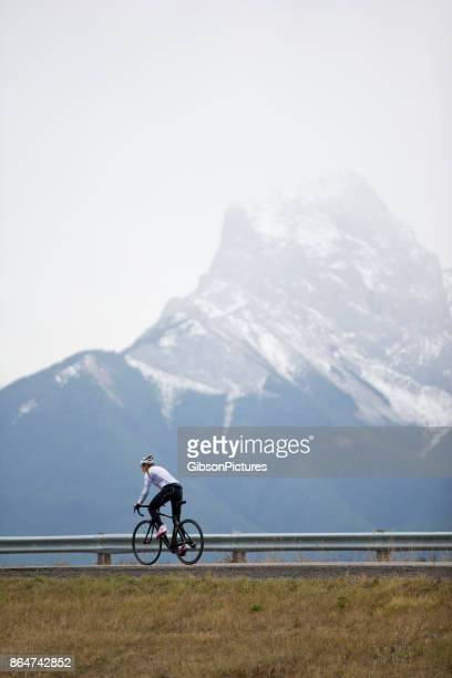 A woman rides her road bike in the Rocky Mountains of Canada.