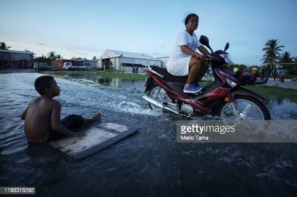 Woman rides her scooter through floodwaters occurring around high tide in a low lying area near the airport on November 27, 2019 in Funafuti, Tuvalu....