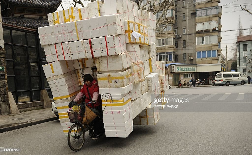 A woman rides her tricycle loaded with p : News Photo