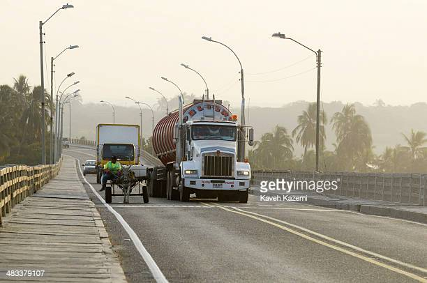 BARRANQUILLA COLOMBIA JANUARY 27 2014 A woman rides on a donkey cart next to a huge lorry on a bridge near the port on January 27 2014 in...