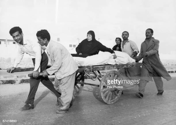 Woman rides on a handcart next to the body of her dead son in Anglo-French occupied Port Said, during the Suez Crisis, 8th November 1956.