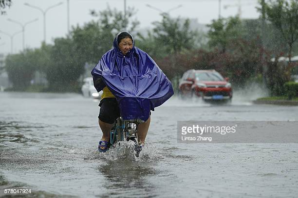 A woman rides on the flooded street in the heavy rain on July 20 2016 in Beijing China Heavy rainfall hit capital Beijing and Beijing Meteorological...
