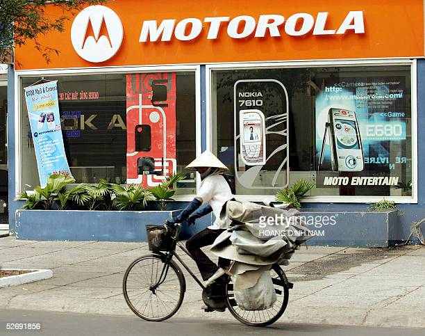 A woman rides past a Motorola handphone shop in downtown Ho Chi Minh city 25 April 2005 Vietnam prepares to celebrate the 30th anniversary of its...