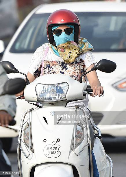 6a8eded4021 A woman rides two wheeler as she covers her face with cloth on a hot  afternoon