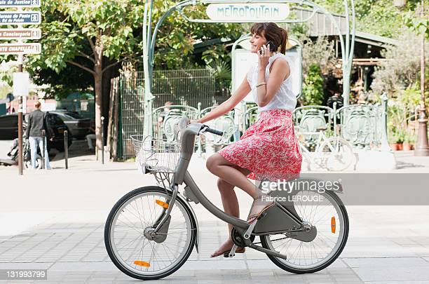 Woman riding a bicycle and talking on a mobile phone, Paris, Ile-de-France, France