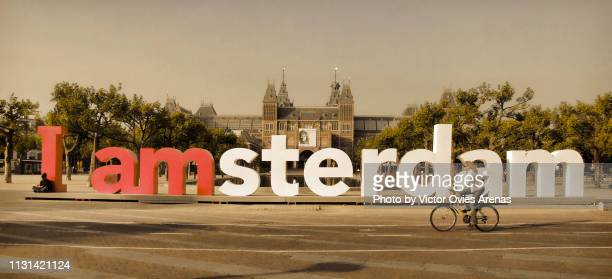 woman riding a bicycle in front of the i amsterdam logo in front of the rijksmuseum in amsterdam, netherlands - victor ovies fotografías e imágenes de stock