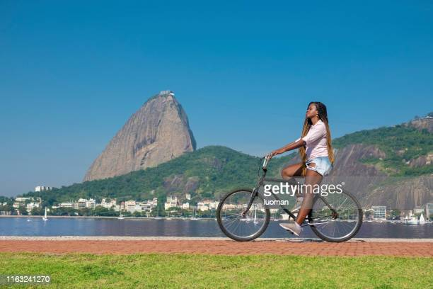 mujer montando en bicicleta frente al pan de azúcar - río de janeiro fotografías e imágenes de stock