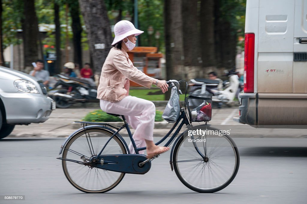 Woman Riding A Bicycle In Ho Chi Minh City, Vietnam : Stock Photo