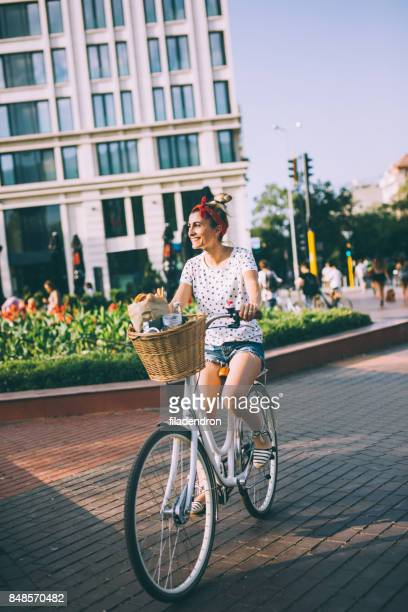 woman riding a bicycle in the city - nassau stock photos and pictures