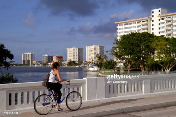 A woman riding a bicycle on a bridge over Lake Boca Raton