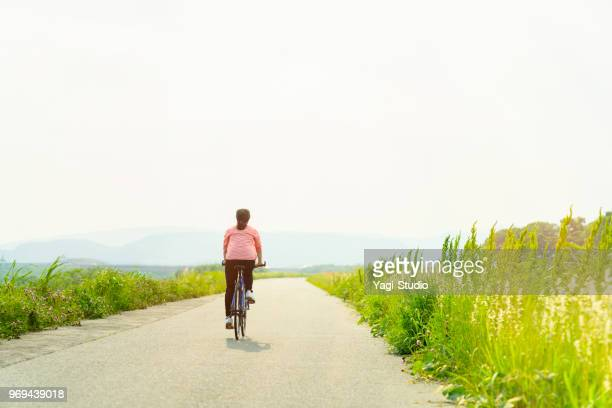 woman riding a bicycle on a road - riva del fiume foto e immagini stock