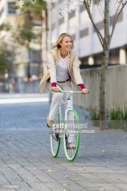 woman riding a bicycle on a street and smiling - adulto de mediana edad fotografías e imágenes de stock