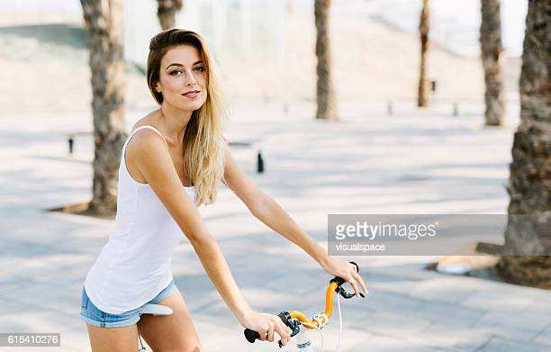 woman riding a bicycle - human powered vehicle stock photos and pictures