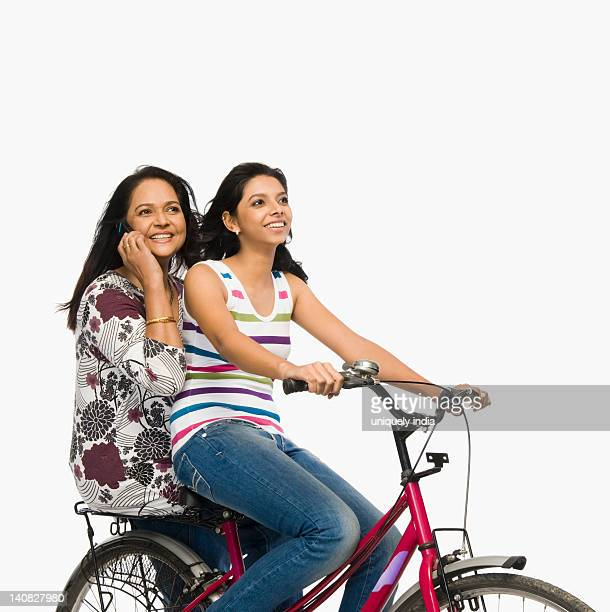 Woman riding a bicycle while her mother talking on a mobile phone