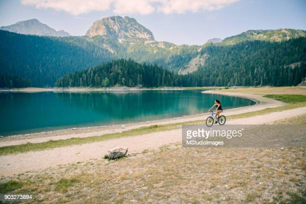Woman riding a bike by the lake.